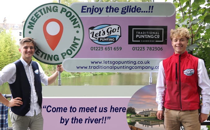 2 young men smile standing either side of a large sign that says meeting point for the punting tours