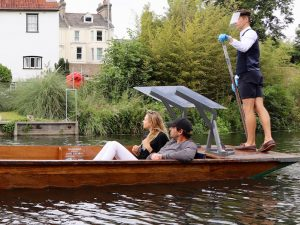 the back of a punt with a chauffeur wearing a protective mask and gloves