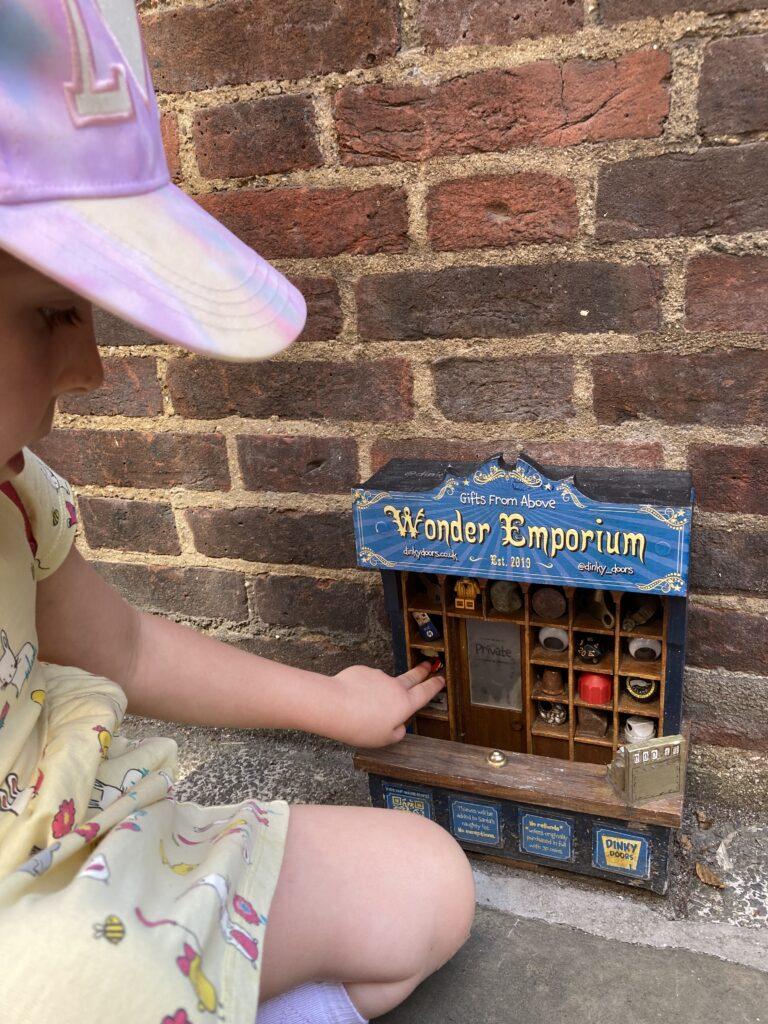 Young girl looking at the Wonder Emporium Dinky Door